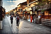 Cyclists on an empty Hanamikoji Dori street in Gion district in morning sunrise before all the shops and restaurants start opening. Hanami-koji, Gionmachi Minamigawa, Higashiyama Ward, Kyoto, Japan