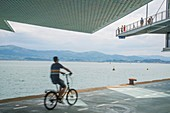 Man riding a bike and view of the bay from Botin Center. Santander, Spain.