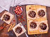 Chocolate muffins and a plate of cherries in their own juice on a brown wooden background, top view.