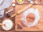 Square wooden kitchen board with rolling pin and wheat flour in a wooden bowl, top view.