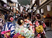Group of teenage girls in bright Yukatas, summer kimonos, walking towards Kiyomizu-dera on Matsubara dori street in Kyoto. Higashiyama, Kyoto, Japan.
