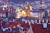 Prague - elevated view of spires of the old town and charles bridge at dusk.