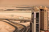 UAE, Dubai, Downtown Dubai, elevated desert and highway view towards Ras Al Khor with Radisson Hotel, dusk.