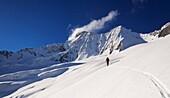 A man skiing uphill on the Disgrazia glacier, Valmalenco, Valtellina, Lombardy, Italy.