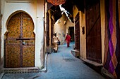 Fes, Morocco, North Africa. Passers in the narrow streets of the medina.