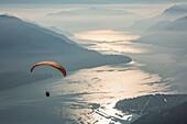 Paragliding over Lake Como and the surroundings mountains. Alto Lario, Como, Lombardy, Italy, Europe.
