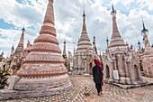 Kakku, Taunggyi, Shan State, Myanmar (Birmania). A woman walking between the 2478 stupas.
