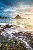 Vagar island, Faroe Islands, Denmark. Coastal rocks with Tinholmur islet at the background at sunset.