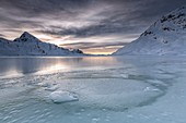 The smooth ice and choppy splits are enhanced by a dark sky clouded by fanciful glazes. White Lake. Bernina Pass. Canton of Graubuenden. Engadine. Switzerland. Europe.