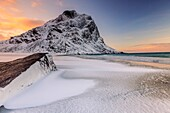 Dawn illuminates the rocks shaped by wind surrounded by fresh snow. Uttakleiv Lofoten Islands Norway Europe.