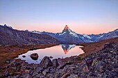 Hikers admire the Matterhorn reflected in the Stellisee at sunrise. Zermatt Canton of Valais Pennine Alps Switzerland Europe.