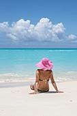 Tourist admires the turquoise Caribbean Sea Jolly Beach Antigua and Barbuda Leeward Island West Indies.
