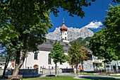 Typical church of alpine village surrounded by peaks and woods Garmisch Partenkirchen Oberbayern region Bavaria Germany Europe.