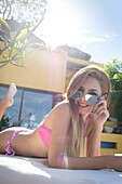 Female teenager in bikini looking cheeky over her sunglasses flirting with the camera, smiling while tanning.