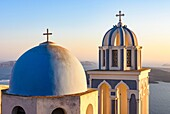 Sunset over a blue domed church on Santorini Island, Cyclades, Greece.