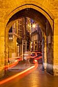 Car light-trails through entry gate to Place de l'Hotel de Ville at night, Aix-en-Provence, France.