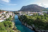Aerial view on Mostar Old Town and Stari Most (Old Bridge) over Neretva river, Bosnia and Herzegovina. Hum Hill on background.