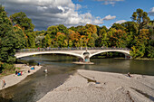 Autumn mood at Kabelsteg along the river Isar, Visitors enjoy the afternoon sun on the gravel banks and the bridge, Munich, Upper Bavaria, Germany