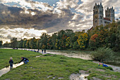 Father playing with his son on the banks of the river Isar, Church of St. Maximilian in the background, passersby standing at the autumnal banks of the river, Munich, Upper Bavaria, Germany