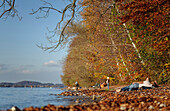 Autumn in Leoni at Starnberger See, a couple lying on the shore enjoying the afternoon sun, in the background further visitors and a bather, Leoni, Upper Bavaria, Germany
