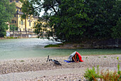 Two man protecting themselves against the rain whilst sitting on a gravel bank in the river Isar, in the background you can see the Muellersche Volksbad, Munich, Upper Bavaria, Germany