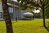 A man playing Frisbee in front of the Futuro-Haus from Matti Suuronen at Pinakothek der Moderne, Munich, Upper Bavaria, Germany