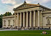 Two young ladys sitting on the grass at Koenigsplatz in front of the Ionische Glyptothek, where further people are relaxing and enjoying the evening, Munich, Upper Bavaria, Germany