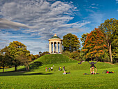 A young couple practicing yoga on the grass in front of the Monopteros in the English Garden in autumn, passersby strolling over the green, Munich, Upper Bavaria, Germany