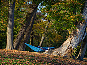 Eine Frau liegt in einer Hängematte und liest ein Buch im herbstlichen Englischen Garten, München, Oberbayern, Deutschland