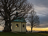 A man sitting at Maria-Dank-chapel at Degerndorf enjoying the sunset over the alps, Muensing, Upper Bavaria, Germany