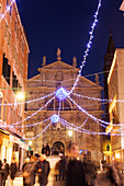 ITALY, Venice. Christmas decorations hangs over Campo San Moise along Calle Larga XXII Marzo. The Chiesa di San Moise is in the center and the front of the Hotel Bauer is on the right.