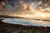 HAWAII, Oahu, North Shore, waves crashing into the rocks at Turtle Bay Resort at Sunset