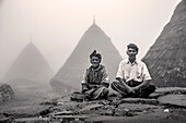 INDONESIA, Flores, two leaders of the Wae Rebo Village sit in front of their residences called Mbaru Niang