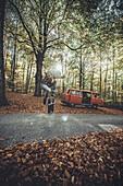 Mann skatet im wald vor VW bus, Aalen, Ostalbkreis, Baden-Württemberg, Deutschland, Europa.