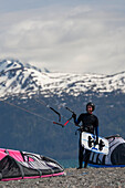 Kite Surfer With Board And Holding Kite On The Beach Of Homer, Southcentral Alaska, USA