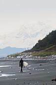 Surfer Holding Surfboard And Walking On Shore Near Yakutat, Southeast Alaska, USA