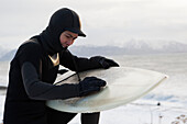 Surfer Waxing A Surfboard In Winter Along Kachemak Bay, Homer Spit, Southcentral Alaska, USA