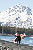 Surfer Walking With Surfboard Along The Kenai Peninsula Outer Coast, Southcentral Alaska, USA