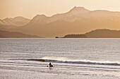 Kayaker Standing On Beach, Kachemak Bay With Kenai Mountains In The Background, Homer Spit, Southcentral Alaska, USA