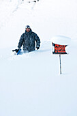 Snowboarder in deep snow on private property, Homer, Southcentral Alaska, USA