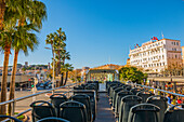 Seats In A Tour Bus With A View Of The Pedestrians, Palm Trees And Buildings In The French Riviera; Cannes, Cote D'azur, France