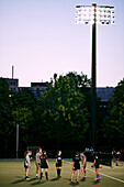 Sports Team Practice On A Field On The University Of Toronto Campus At Dusk; Toronto, Ontario, Canada