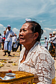 A Senior Women At A Religious Ceremony On The Beach; Bali, Indonesia