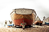 A wooden motorboat sits on the shingle beach with buildings in the background; England