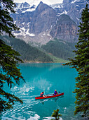 A red canoe in Moraine Lake with a cliff of the Canadian Rocky Mountains along the shoreline; Lake Louise, Alberta, Canada