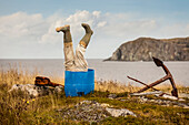 Sculpture of man's legs wearing rubber boots upside down in a barrel along the Atlantic coast; Newfoundland, Canada