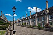 Historic houses on Vicars' Close with a street lamp and cobblestone street. Built between 1348 and 1430, Vicars' Close is claimed to be the oldest purely residential street with its original buildings all surviving intact in Europe; Wells, Somerset, Engla