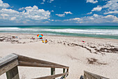 Sunbathers sit on the sand of Pelican Beach with a colourful umbrella looking out to the Atlantic ocean, and wooden steps with railing in the foreground; Satellite Beach, Florida, United States of America
