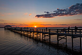 People standing on a pier as the sun sets over the Indian River; Indialantic, Florida, United States of America