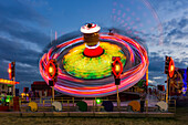 Amusement park ride glowing at dusk with colourful lights and motion blur; Newcastle Upon Tyne, Tyne and Wear, England